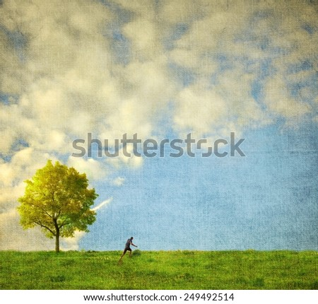 Lone tree with human figure running - stock photo