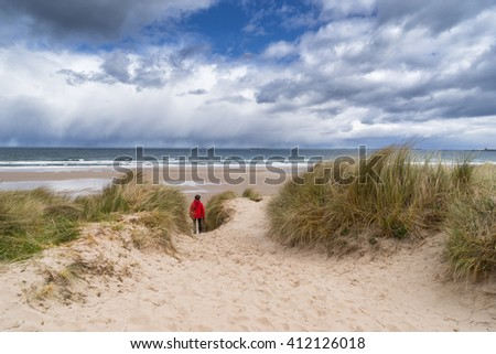 Lone walker on the sand dunes of Bamburgh in  Northumberland