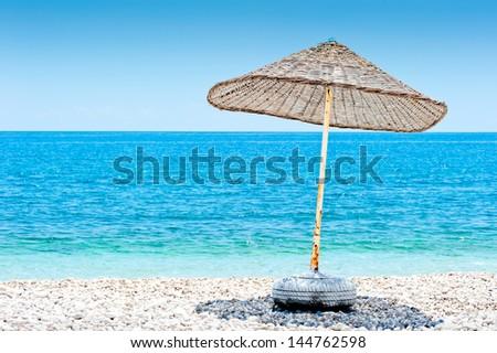 lone wicker umbrella on the beach - stock photo
