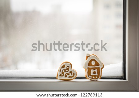 Loneliness. Christmas gingerbread cookies on the winter window with snow with copy space for your text