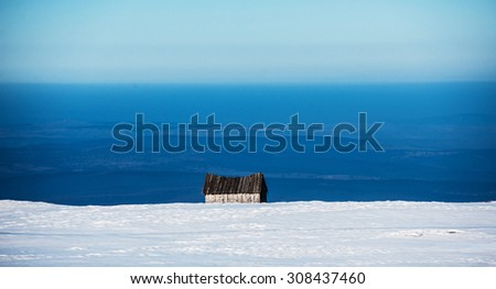 Loneliness concept - abandoned house on a mountain hill surrounded by snow - stock photo