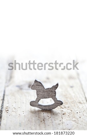 Loneliness concept: wooden rocking horse on wooden background with copyspace - stock photo