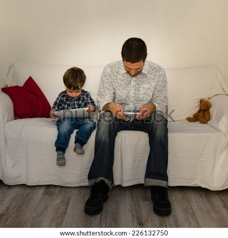 Loneliness of baby and father playing with tablet and phone on a white sofa both without care of each other with red pillow and little bear - stock photo