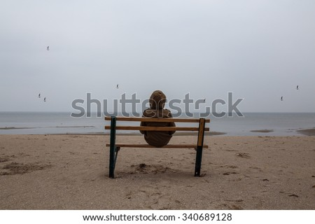 Loneliness teenager sitting on a bench at the sea shore - stock photo