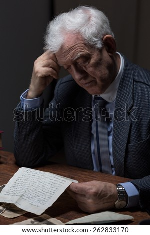 Lonely aged man reading old letter from a lover - stock photo