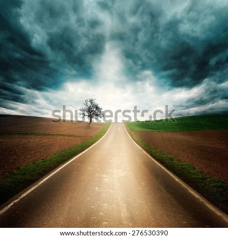 Lonely and moody road through empty fields with dramatic sky, dark clouds, interesting light and symmetrical composition