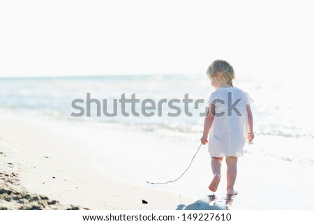 Lonely baby walking at seaside . rear view