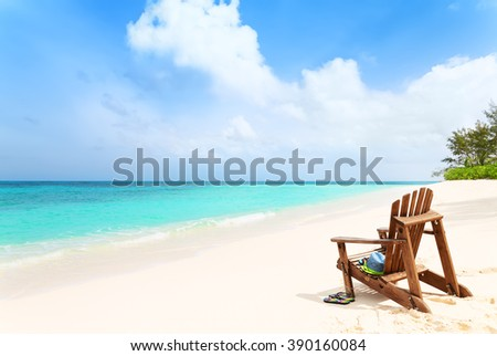 Lonely beach chair with hat and slippers at tropical beach, summer holiday concept   - stock photo