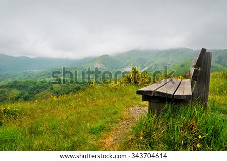 Lonely bench on a hill with mountain scenery around - stock photo