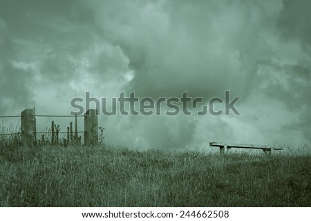 lonely bench seat on a hill top with summer rain clouds, New Zealand