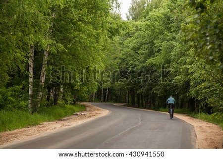 Lonely bicycle riders on a asphalt park road