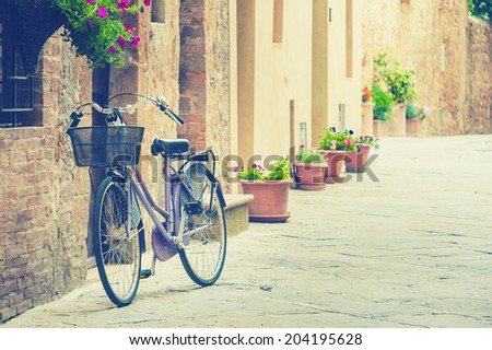 Lonely bike awaiting its owner, based on the old wall in Tuscany, Italy - stock photo