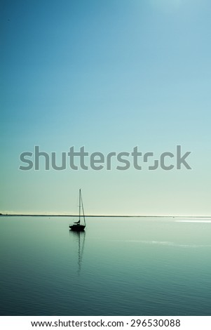 lonely boat on calm sea - stock photo