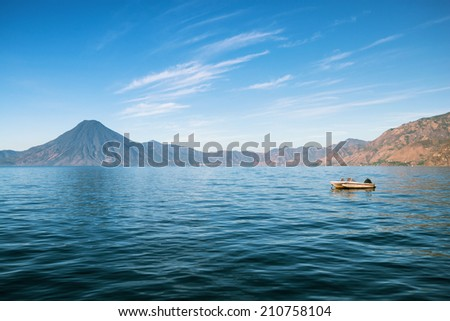 Lonely boat on the lake Atitlan in Guatemala with volcano in the background - stock photo