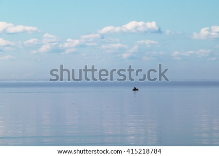 Lonely boat with fisherman on board against the misty horizon with reflections of sky and clouds in still water, blue and a bit rose. - stock photo