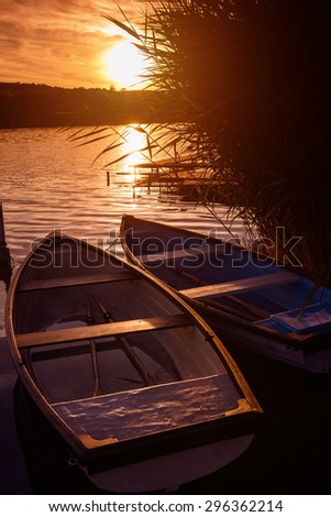 Lonely boats at sunset - relax - stock photo