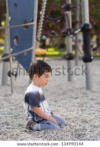 Lonely bored child sitting on ground in playground. - stock photo