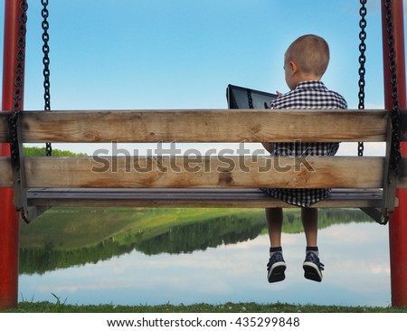 lonely boy on a swing with the tablet. psychology concept. - stock photo