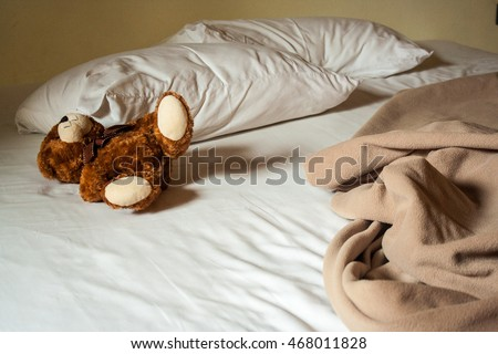 Lonely brown Teddy Bear lying on the bed with white sheets. Concept about waiting for someone and loneliness.