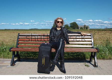 lonely bus stop at countryside with women on bench - stock photo