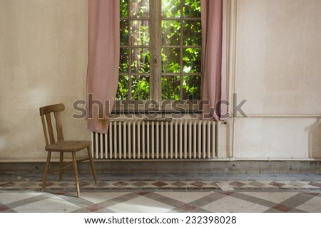 lonely chair by window in creepy abandoned building - stock photo