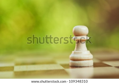 lonely chess pawn on board background - stock photo