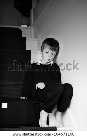 Lonely child sitting on the stairs. - stock photo