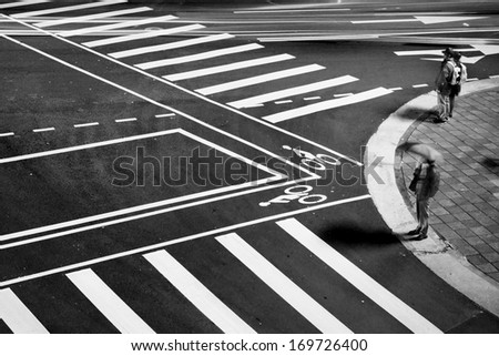 Lonely city street, an old lady and one couple waiting in front of Zebra Crossing, in the night of rainy Taipei, Taiwan. - stock photo