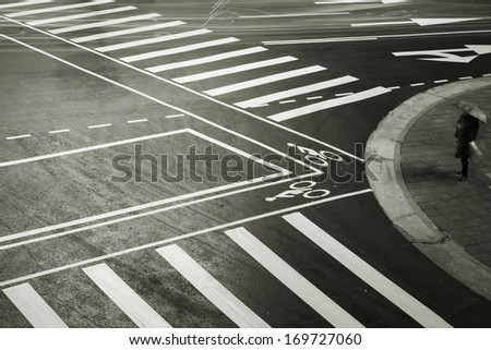 Lonely city street, an old lady waiting in front of Zebra Crossing, in the night of rainy Taipei, Taiwan. - stock photo