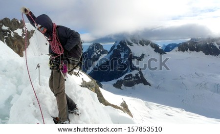 Lonely climber picking up a rope over a ridge while climbing Jungfrau moutain. Mönch and Eiger summits can be found far beyond, Switzerland  - stock photo