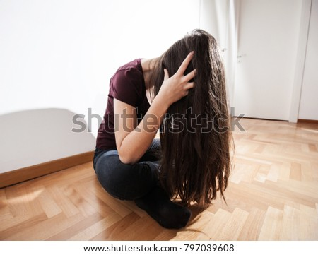 Lonely Depressed young woman sitting on floor in empty dark room, female suffering from depression.