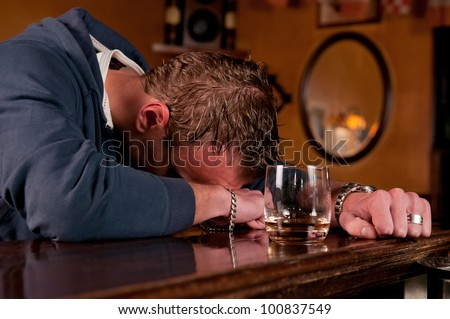 Lonely drunk man who has had one too many glasses of alcohol at the bar and has passed out on the countertop