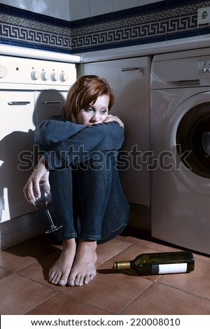 lonely drunk sick woman sitting on kitchen floor in depression feeling miserable holding his legs in barefoot looking desperate in alcoholism and drinking to forget concept - stock photo