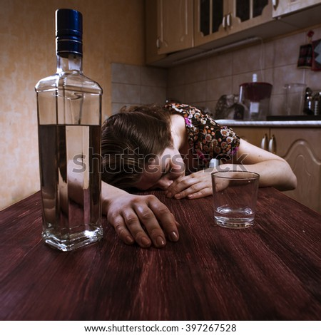 Lonely Drunk woman sleeping on the table on kitchen. Female alcoholism. Selective focus.