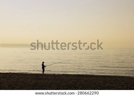 Lonely Fisherman on the Beach at Sunrise Time.  Mediterranean Sea, Greece.