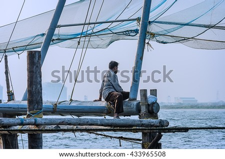 Lonely fisherman sitting on a wooden fishing platform port Cochin, South India. - stock photo