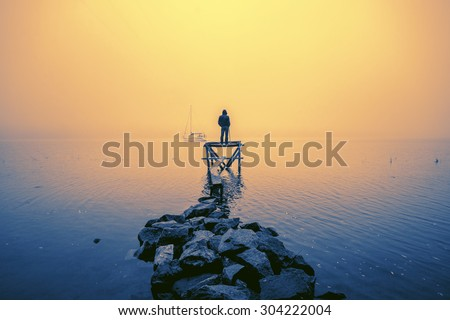 Lonely fisherman, standing on the wooden jetty in the autumn foggy river with stones gangway. Yacht on the background. - stock photo