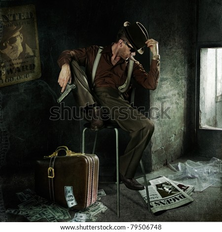 Lonely gangster with gun and suitcase full of money. Art-photo in original style