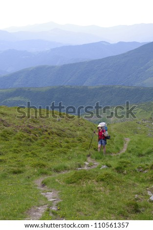 Lonely girl climbs into the mountains along the path, her backpack and it is based on trekking sticks - all against the backdrop of green mountains