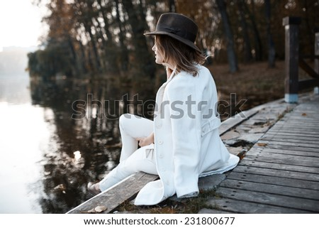 Lonely girl in cloudy weather sits near the water and looks into the distance