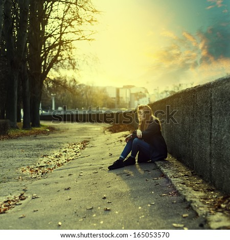 Lonely girl in the city at sunset - stock photo
