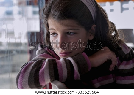 Lonely girl looking out the window - stock photo