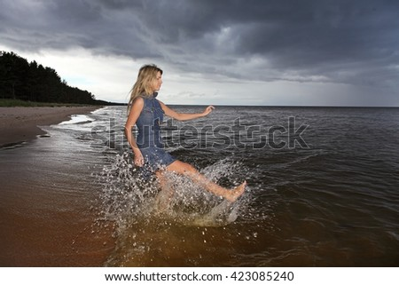 lonely girl playing with water on a beach with stormy sky - stock photo