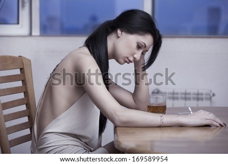 lonely girl sitting at a table with a glass of whiskey and a cigarette - stock photo