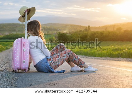 Lonely girl sitting on the road next to her suitcase - stock photo