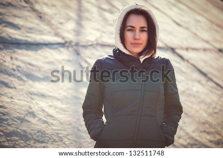 Lonely girl standing in front of concrete wall in sunny day