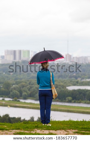 lonely girl under an umbrella on a background of the river and the city - stock photo