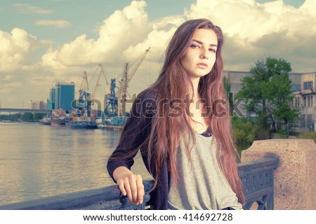 Lonely girl waiting for your. Wearing light gray shirt, black jacket, an young american woman standing by metal fence on pier in New York, frowned, with port cranes on background. Instagram effect. - stock photo
