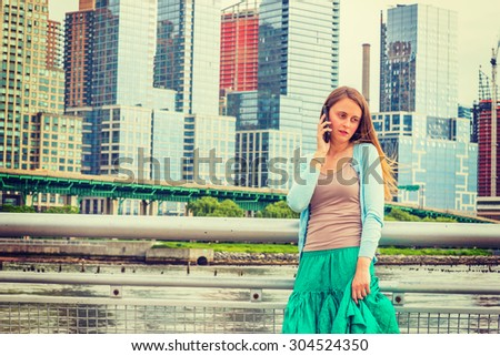Lonely girl wants someone to talk. Wearing light blue sweater, green skirt, an American woman standing by metal fence on pier in New York, sad, depressed, listening to cell phone. Instagram effect. - stock photo