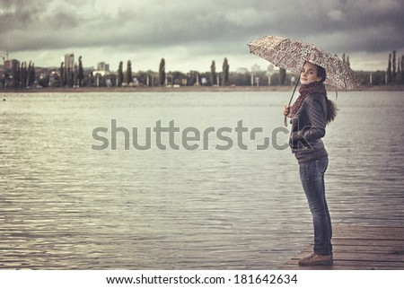 lonely girl with an umbrella in the city reservoir - stock photo
